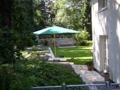 Garten mit Hochbeet und großer Rasenfläche